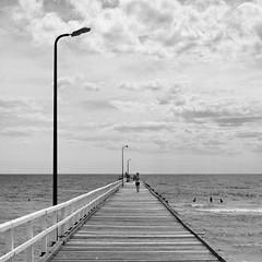 seaford pier {explored #493 - dropped} (Seakayem) Tags: blackandwhite bw pier noir sony 28mm australia melbourne victoria squareformat seaford f28 slt maxxum portphillipbay a55