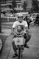 Not yet ready to ride (Go-tea ) Tags: canon eos 100d 50mm street city hurban qingdao huangdao outside outdoor bw bnw blackwhite blackandwhithe black white china life chinese asia asian people portrait byke bicycle both together fater son happy scared hat smile tshirt glasses up down mouvement fast slow family poeple