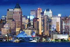 Skyscrapers in New York City (scott photos) Tags: nyc newyorkcity longexposure ny newyork night buildings lights nikon ship skyscrapers dusk manhattan midtown hudsonriver aircraftcarrier nikkor spaceshuttle 80200mm ussintrepid 80200mmf28d 80200mmf28 80200mmf28dnew byscottphotos d300s