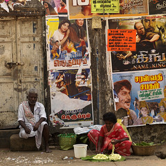 Man Sitting Next To His Wife Making Flowers Garland In Front Of Bollywood Posters, Madurai, India (Eric Lafforgue) Tags: poverty street people india cinema colour leaves advertising square outside outdoors day sitting basket text movieposter bollywood hindu groupofpeople sari madurai tamilnadu squatting darkhair grayhair oneman direstraits urbanscene wickerbasket onewoman indianpeople flowergarland twoadults twoperson padlockeddoor bengaliwriting workingscene bengalicharacter twomatureperson a03312