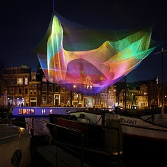 Light sculpture Amsterdam 1.26 in the enchanting limelights (Bn) Tags: city pink blue winter light sunset red urban sculpture orange holland colour reflection green art net water colors amsterdam yellow festival architecture night river lights hall rainbow topf50 colorful purple wind walk bridges waterloo hour sail janet shape topf100 mokum waterlooplein artworks amstel 126 muziektheater stopera projections sqaure blauwbrug echelman artisticexpression 100faves 50faves illiminated lichtfestival reshapes