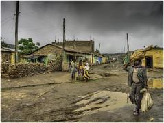 Aksum Street View (Luc V. de Zeeuw) Tags: aksum dirt dirtroad ethiopia fruit man puddleofwater rainy selling streetview tigray