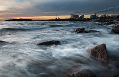 Rocks & waves (- David Olsson -) Tags: winter sunset lake seascape motion cold industry water clouds landscape flow movement nikon rocks waves branch factory sundown cloudy sweden stones smoke fabrik windy newyear pollution firstday flowing chimneys vnern lively storaenso dx hammar vrmland 1635 awash 1635mm lakescape skoghall environmentaldegradation 2exposures d5000 manualblend manuallyblended davidolsson skoghallsverken 1635vr skoghallsbruk grytudden