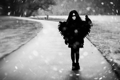 She was a crow (Kilkennycat) Tags: portrait blackandwhite bw snow bird girl lensbaby canon children wings child serious feathers muse snowing crow 500d kilkennycat t1i ryanconners