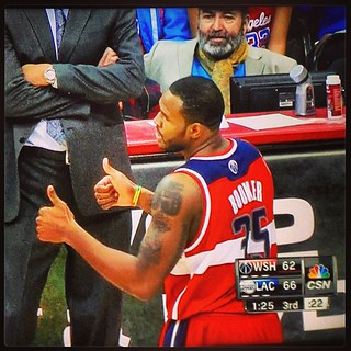 Trevor Booker gives 2 thumbs up as an odd bearded man with a fashion scarf gazes in his direction.