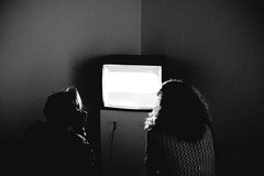 Idiot Box (matt.hagge) Tags: fujifilm fujinon x100t rangefinder handheld 23mm 35mm f2 f36 digital apsc camera street photography blackandwhite monochrome indoor tv television photo art gallery light dark screen women two people person harsh shadows black vsco lightroom