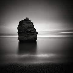 Loner (Andy Brown (mrbuk1)) Tags: ocean longexposure light shadow sea sky cloud seascape reflection beach water rock contrast dark square dawn mono blackwhite moody seagull horizon shingle stack erosion devon shore solitary vignette luminance firstlight splittone neutraldensity