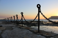 Rock and Chain - (Explored!) (Odkaella) Tags: ocean blue light sunset sea sky orange sunlight seascape color colour reflection beach nature water silhouette metal stone backlight clouds contrast canon fence reflections newcastle landscape eos evening coast seaside rocks waves afternoon sundown horizon january australia chain explore loops coastal nsw refraction newsouthwales hunter ripples hoops links huntervalley explored lastrays 60d canoepool