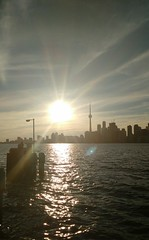 Let the Sun Shine Through (Georgie_grrl) Tags: harbourfront lakeontario waitingfortheferry ontheisland sky clouds sun cntower toronto ontario embracetheflare water lake skyline