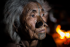portrait in front of the fire, Apatani tribe, ziro, arunachal pradesh (anthony pappone photography) Tags: old travel portrait india tattoo canon hair fire spirit piercing oldwoman tribe ethnic ritratto fuoco arunachal etnic arunachalpradesh animist ziro apatani animisti apatanitribe donyipolo plateinnose