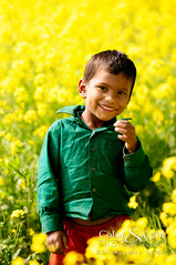 Smile (Neerod [ www.colorandlightphotography.com ]) Tags: flowers boy portrait flower happy stand kid child bangladesh bosila