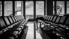 Waiting (Jens Haggren (mostly off)) Tags: olympus em1 waiting airport chairs reflections view windows bw mono