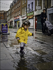Puddle Stomper (Sven Loach) Tags: street uk england urban playing london wet girl smile rain yellow puddle kid nikon child britain candid perspective mother streetphotography shops colourful raincoat clerkenwell playful pram exmouthmarket d5100