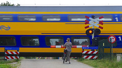Railway crossing lady (andzwe) Tags: train railwaycrossing levelcrossing spoorwegovergang steenwijk lady hat muts bike waiting wacht wachten ns trein wache wait panasonicdmcgh4