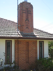 The Red Brick Stepped Chimney of an Art Deco Villa - Leongatha (raaen99) Tags: door 1920s roof chimney house building brick home window architecture facade garden town 1930s fireplace cement cottage entrance australia stainedglass victoria moderne tiles porch villa artdeco residence deco 20thcentury markettown rounded nook feature 30s streamline portico stepped 20s redbrick entranceway gippsland countryvictoria vestibule decoarchitecture modernhome metroland domesticarchitecture twentiethcentury streamlinemoderne countrytown southgippsland streamlinemodernearchitecture artdecoarchitecture interwar leongatha tilesroof provincialvictoria fibrocement dairytown roundedwall nookwindow interwararchitecture artdecostainedglass sheetingfibrofibro sheetingterracottaterracotta artdecostainedglasswindow
