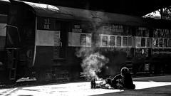 Repas de midi en gare de New Delhi. (Gilles Daligand) Tags: inde india newdelhi gare railwaystation clochard downandout djeuner tohavelunch feu fire quai platform solitude alone noiretblanc bw monochrome sony hx50v