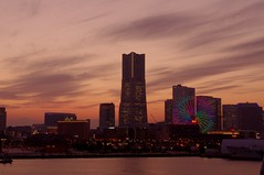 Minato Mirai as the sun goes down (runslikethewind83) Tags: sunset sea sky orange cloud building japan skyline clouds buildings bay march fuji pentax landmark ferris ferriswheel  yokohama  kanagawa minatomirai    nihon landmarktower mtfuji      osanbashi  2013