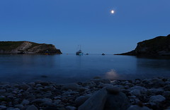 Stillness (music_man800) Tags: lulworth cove dorset uk united kingdom jurassic coast sssi national trust durdle door harbour natural england area outstanding beauty beach stony stones water sea boats boat pebbles long exposure tripod night dusk sunset blue hour evening bluehour photography moon reflections reflection mirror cliffs silhouette creative edit gimp2 gimp light pretty beautiful nature sky outdoor outdoors sundown