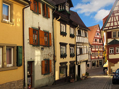 Picturesque Old Town of Bad Wimpfen (Batikart) Tags: road street old city november flowers autumn houses windows light shadow urban orange plants green fall lamp colors car sunshine yellow architecture canon buildings germany bench outdoors deutschland town alley europa europe day doors colours village bright herbst citylife tranquility sunny warped medieval romance historic journey stadt shutters blinds romantic historical recreation lantern relaxation cobbles ursula idyllic centrum variation halftimbered 2012 skew canonpowershot sander g11 fachwerkhaus badenwrttemberg swabian badwimpfen 100faves 2013 200faves cobbledstonestreet batikart outofsquare