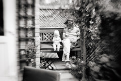 Precious Grandad time (Simon in Southend) Tags: lensbaby composer lensbabies seeinanewway sony a6000 alpha 6000 ilce6000 bw black white mono monochrome lightroom lr5 nik analog efex pro2 glow blur blurry blury bokeh selective focus creative bend smooth grandad grandaughter daughter girl little toddler cute petit beautiful love lovely precious moment moments garden family child children wonder bench leaves foliage framed tressle trestle outside