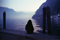 Souvenirs D'Un Autre Monde (The Shape Of Despair) Tags: light sunset sun mist lake mountains cold film girl souvenirs haze garda riva dream silence doom trento 28 swallow dim monde expired 35 nikonf trentino dun ftn autre photomic alcest