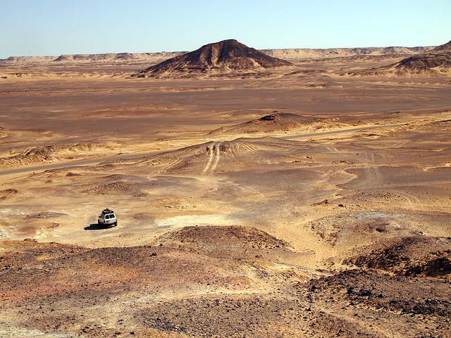 <p>ピラミッド型の黒砂漠の小山に登る。<br/>下に見えるのが私たちの四駆。</p>