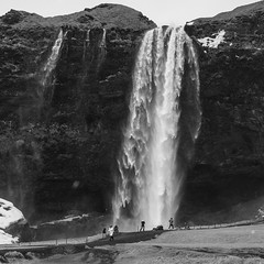 nature dwarving man (lunaryuna) Tags: iceland southiceland landscape waterfall seljalandsfoss storm wind whippedupwaterfall visitors naturedwarvingman blackwhite bw monochrome winter season seasonalwonders lunaryuna