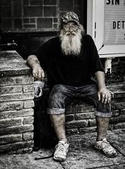 Street (Radiogal73s) Tags: man beard mustache hat glasses black shirt bluejeans white sneakers backpack plastic bag sign church sidewalk