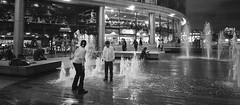 Playing by the water fountains (Florian Btow) Tags: london uk united kingdom england great britain city night water fountain kids playing wet 16x7 black white street photography wide angle
