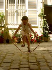 Nour jumps rope (maralina!) Tags: playing girl childhood kid child courtyard jeunesse cobblestone littlegirl chic enfant nio fille jumprope petit cour pave jeune fillette petitefille