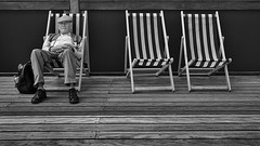 On The Pier (Peter.Bartlett) Tags: street people urban blackandwhite holiday man monochrome mono pier blackwhite seaside sitting unitedkingdom candid sony streetphotography oldman nik alpha 700 bournemouth deckchairs blackdiamond flatcap ordinarypeople sittingman blackwhitephotos sonyalpha streetphotographyurban alpha700 sonyalpha700 niksilverefex