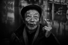 let me spin you a tale (~mimo~) Tags: china street old portrait people blackandwhite man face hat asia shanghai cigarette smoke streetphotography streetportrait story tale alleys lanes teashop qibao mimokhair Potd:country=menaen