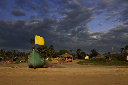 Arambol Beach with a green boat, a yellow flag, a beach shack and a winter