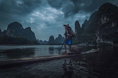 Paddling his raft (Syahrel Azha Hashim) Tags: singleexposure mountains tokina shallow simple dramaticsky single shadow touristattraction conventional humaninterest handheld colorimage vacation destination china moment fishing d300s elder uwa beard portrait lantern water unique 11mm raft chinese details portraiture xingping ultrawideangle bird traditional dof culture bamboo detail nikon liriver holiday clouds getaway standing paddling paddle hat oneperson traditionalclothing bambooraft fishermen naturallight scene colorful river cormorants iconic syahrel mountain guilin colors birds light travel oldman fisherman