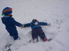 One does a snow angel, the other quickly grabs snow to throw on him..