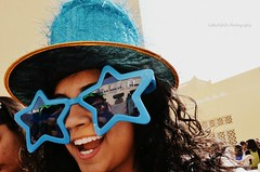 joy. (Min9ahil) Tags: blue wild people girl smile up hair festive fun glasses crazy nikon close faces happiness curls ups curly laugh saudi arabia huge accessories cheerful dslr riyadh rejoice felicity glee joyous feral maniac potraits carnivals starshaped phtoography d5100 min9ahils