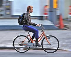 Upright and orange (jeremyhughes) Tags: street urban orange woman motion london bike bicycle cycling movement nikon highheels cyclist boots sigma redhead rack backpack commuter commuting ulock upright redhair panning leatherjacket stylish kickstand knapsack fashionable dynamo mixte chaincase orangebike d700 velocouture cyclestyle