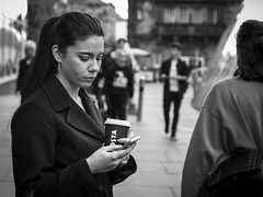 Clouds In Her Coffee (Leanne Boulton) Tags: people monochrome depthoffield urban street candid portrait portraiture streetphotography candidstreetphotography candidportrait streetlife woman female face facial expression look emotion feeling mood coffee tea mobile phone ponytail distraction thoughtful tone texture detail bokeh natural outdoor light shade shadow city scene human life living humanity society culture canon 7d 50mm black white blackwhite bw mono blackandwhite glasgow scotland uk