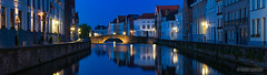 Bruges Canal at Dusk (Darby Sawchuk) Tags: city travel bridge blue vacation urban panorama holiday reflection water night photography lights evening canal cityscape quiet belgium belgique dusk brugge panoramic medieval illuminated worldheritagesite hour bruges serene lit channel waterway travelphotography spiegelrei