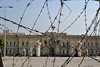 Abdeen Palace behind barbed wire. (Stationary Nomads) Tags: building wall painting graffiti democracy flag president protest egypt palace presidential cairo revolution egyptian barbedwire government martyr martyrs revolutionary mubarak tahrir streetbattle jan25 morsi abdeen mohammedmahmoudstreet