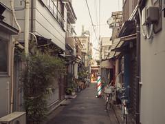 Barber pole is standing (kasa51) Tags: japan digital tokyo alley olympus backstreet omd 自転車 barberpole 月島 路地 裏通り 小路 f4056 em5 urbanarte 横丁 918mm mzuiko 床屋のポール