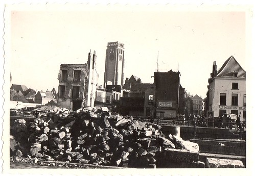 Found photo showing WW II rubble & bombing destruction of a (possibly) French canal and commercial area with a rectangular / Romanesque clock tower in the background.