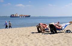 7045 Elbufer bei Stade / Containerschiff auf der Elbe - Strandbesucher in Liegen / Liegesthle im Sand in der Sonne - Spaziergnger. (stadt + land) Tags: sand architektur hafen sonne elbe stade hanse hansestadt geschichte historisch liegen containerschiff liegesthle spaziergnger schwinge strandbesucher
