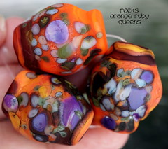 Rocks Orange Ruby Queens (Laura Blanck Openstudio) Tags: openstudio openstudiobeads handmade lampwork glass beads bead set jewelry fine arts art artist artisan made usa big rocks pebbles nuggets faceted stones whimsical funky odd organic abstract earthy colorful multicolor speckles frit transparent winner show festival published murano warm matte etched frosted glow opaque orange coral lilac lavender purple violet grape plum burnt umber green ruby rubino maroon burgundy bordeaux wine