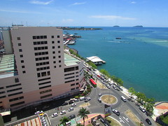 Waterfront In Kota Kinabalu City Centre (thienzieyung) Tags: city travel trees windows shadow sea bus cars water lines boats islands coast waves tour waterfront view traffic empty centre parking horizon roundabout cities places roofs vehicles shore malaysia land arrows boardwalk kotakinabalu geography roads sabah plot birdseye lanes wismamerdeka segama aftenoon thienzieyung