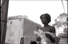 Dakar, Senegal. November 2012 (Flat Twin) Tags: africa street blackandwhite film public girl monochrome bread mono streetphotography streetscene 150 apx100 senegal dakar mm van agfa rodinal rodinal150 nikonf magnum mif inpublic nikkors flattwin streetsnap 35cm minervaoil nikkors35cmf28 moibrahimfoundation