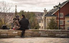 Talk and Whisper (bonaphoto) Tags: camera trees windows chimney sky woman cloud house mountain canada man cold building tree brick love lamp smile stone wall bench bag beige nikon couple warm sitting arch village cloudy quebec branches coat talk overcast romance conversation funnel monttremblant toning canoneos7d d7000 canonef2470mmf28lisiiusm