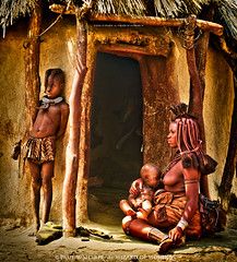 Himba Family by the Door of Their Clay Hut (Wizard of Wonders) Tags: africa wood original boy people woman canada black heritage tourism home girl dreadlocks female vancouver standing naked children person beads sticks women infant breast village child bc looking desert mud natural native african unique branches traditional north innocent decoration mother culture diversity dry tribal hut clay nomad shack curious tradition tribe ethnic youngster namibia cultural authentic himba opuwo kaokoland