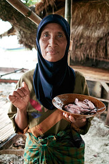 Want some squid, mister? (tsiklonaut) Tags: world travel sea portrait food woman brown beach rural scarf pose indonesia island seaside holding focus bokeh head muslim sigma plate tint lips cover squid experience offering tropical sunburn seafood tropic local positive boiled lombok serving indonesian sarong regional hold bungalow kuta delicacy saar serve discover foveon x3   indoneesia  dp2s tsiklonaut lombokian