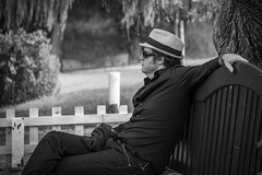 Cool dude (Bilderschachtel Photography) Tags: restaurant wine grootconstantia capetown southafrica streetphotography citylife streetportrait portrait monochrome bw blackandwhite bench sunglasses hat cool relaxed outdoor city garden street people man canon flickr africa shades